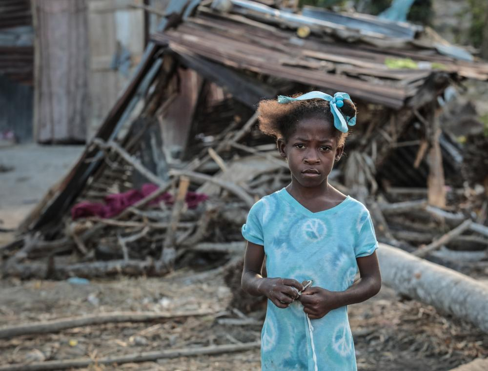 A young caribbean girl standing in front of the rubble caused by Hurricane Maria