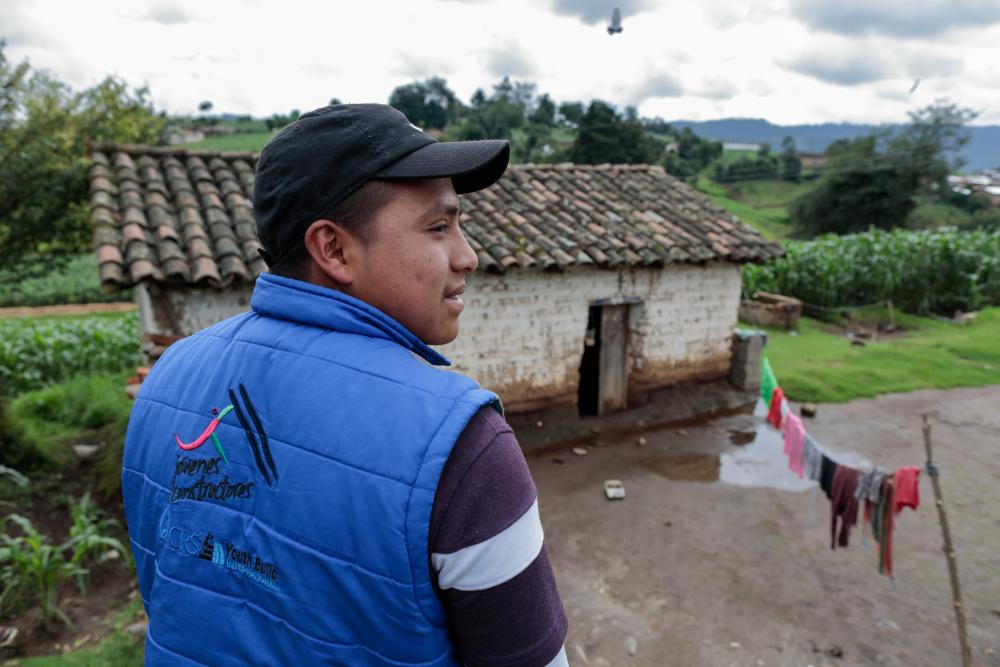Guatemalan beneficiary looks over rural landscape.
