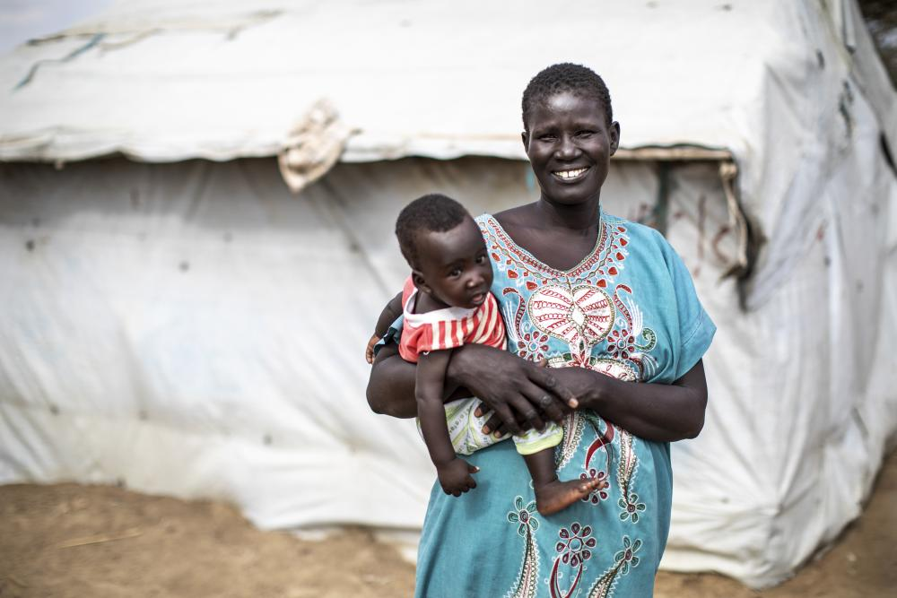 Woman holding child outside temporary housing in South Sudan