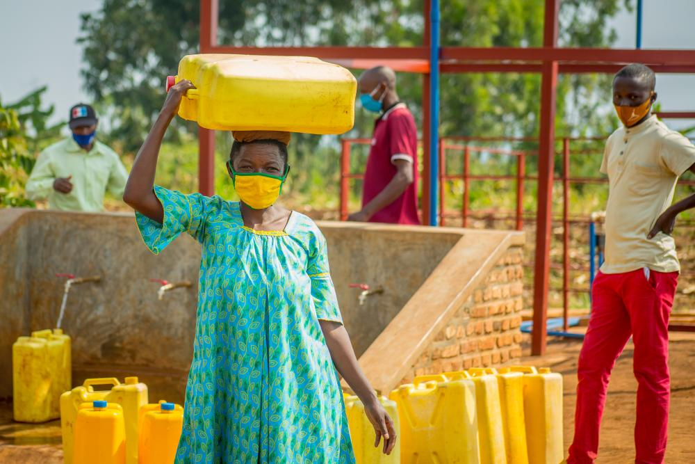 Rwandan woman carrying jug of water