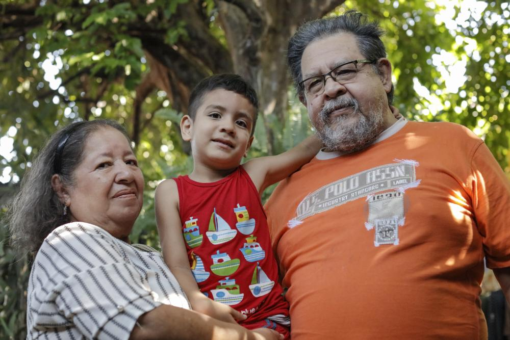Man, woman and great grandchild from El Salvador smile for photo