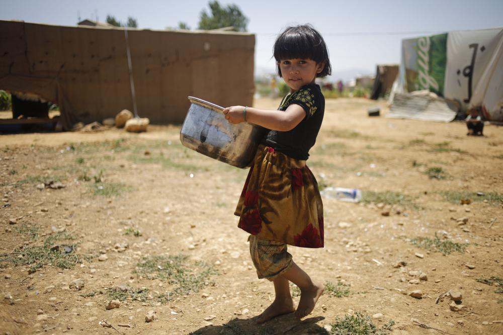A girl carries a pan of water so that she and her six sisters can wash their hair at an informal refugee settlement in Qab Elias in Lebanon's Bekaa Valley.